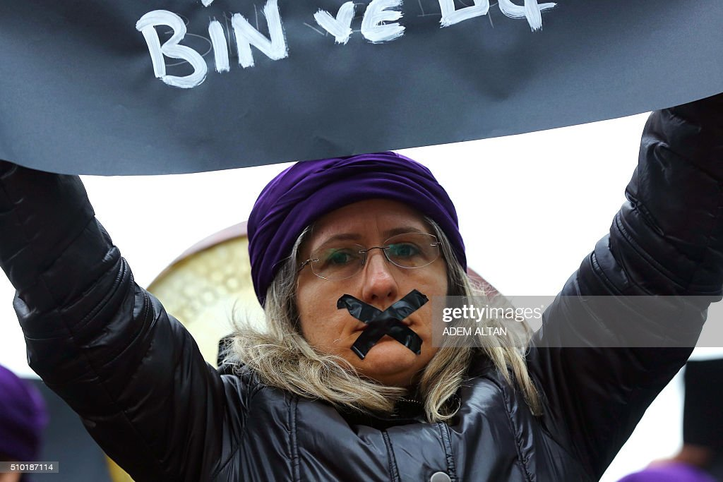Turkish members of the 'One Billion Rising' movement and human rights activists, hold placards condemning violence and injustices against women during a mass action on Valentine's Day in Ankara, on February 14, 2016. / AFP / ADEM ALTAN