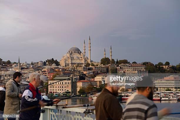 Turkish men fishing on Galata Bridge over Golden Horn with Suleymaniye Mosque Istanbul