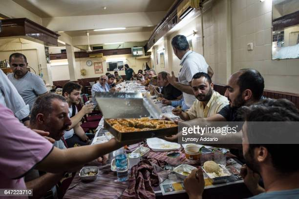Turkish men share an Iftar dinner at a restaurant on a side street off Naci Professor Sensoy Avenue in the Fatih neighbourhood in Istanbul Turkey...
