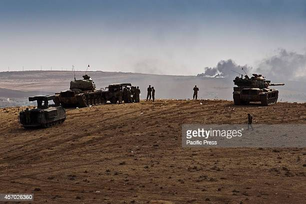 Turkish military troops watching the onslaught battle as the US and coalition forces make airstrikes on the key positions of ISIS allowing the YPG to...