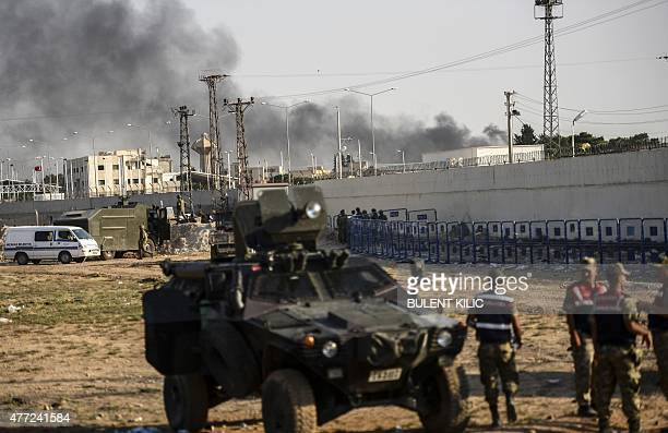 Turkish military trucks and soldiers are seen near the Akcakale crossing gate between Turkey and Syria at Akcakale in Sanliurfa province on June 15...
