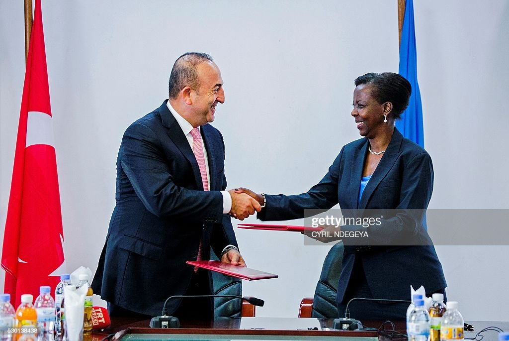 Turkish Minister for Foreign Affairs Mevlut Cavusoglu (L) and Rwandan Minister for Foreign Affairs Louise Mushikiwabo (R) shake hands as they exchange folders after the signing of different Memorandum of understanding (MOU) in Kigali on May 31, 2016. Rwanda-Turkey agreements are expected to strengthen economic ties between the two countries through trade promotion, co-ordination, as well as information, skills and knowledge sharing. Cavusoglu also officially opened the new Turkish embassy in Kigali. / AFP / CYRIL