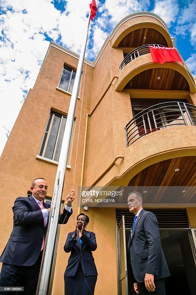 Turkish Minister for Foreign Affairs Mevlut Cavusoglu (L), flanked by his Rwandan counterpart Louise Mushikiwabo, raises the Turkish flag at the new Turkish Embassy in in Kigali on May 31, 2016. Rwanda-Turkey agreements are expected to strengthen economic ties between the two countries through trade promotion, co-ordination, as well as information, skills and knowledge sharing. Cavusoglu also officially opened the new Turkish embassy in Kigali. / AFP / CYRIL