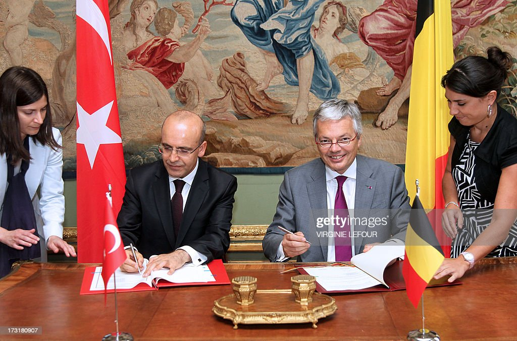 Turkish Minister of Finance Mehmet Simsek (L) and Belgian Vice-Prime Minister and Foreign Minister Didier Reynders pose during the signing of an agreement between Belgium and Turkey to avoid double taxes, at the Egmont Palace in Brussels, on July 9, 2013.