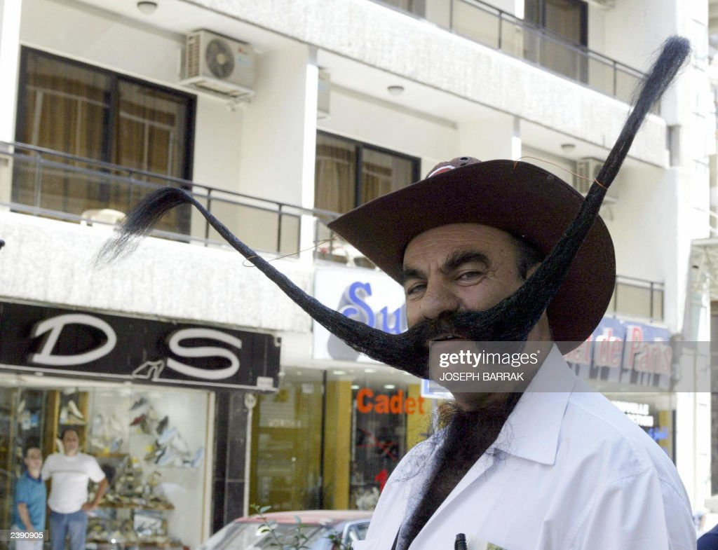 Turkish Mohammed Rashid, 62-year-old, poses for a picture 10 June 2003 in Beirut. Rashid who displays his moustache in Beirut, said his 1.6-meter-long moustache placed him in Guinness Book as the man with the world's longest moustache. Rashid, an architect, said he has not cut his moustache for about 10 years. He charges five US dollars for anyone who wants to take a souvenir picture with him. Rashid, who is touring the world, said he uses the money to cover expenses of the trip. AFP PHOTO / Joseph BARRAK
