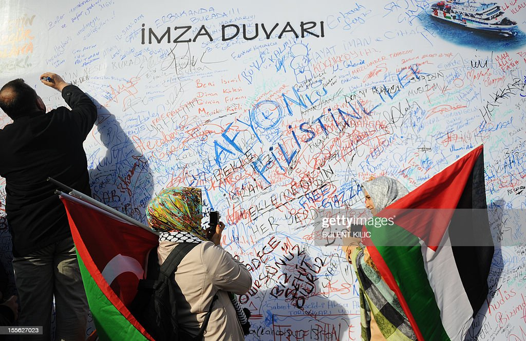 A Turkish muslim man signs a board as women hold Palestinian flags during a demonstration outside the courtroom on November 6, 2012, in Istanbul. Four Israeli ex-military chiefs went on trial in absentia in an Istanbul court over a deadly 2010 raid on a Gaza-bound Turkish ship in what Israel branded a 'show trial' by its former ally. Prosecutors are seeking life sentences for the four over the night-time assault in international waters in the Mediterranean Sea that plunged relations between Israel and Turkey into deep crisis.
