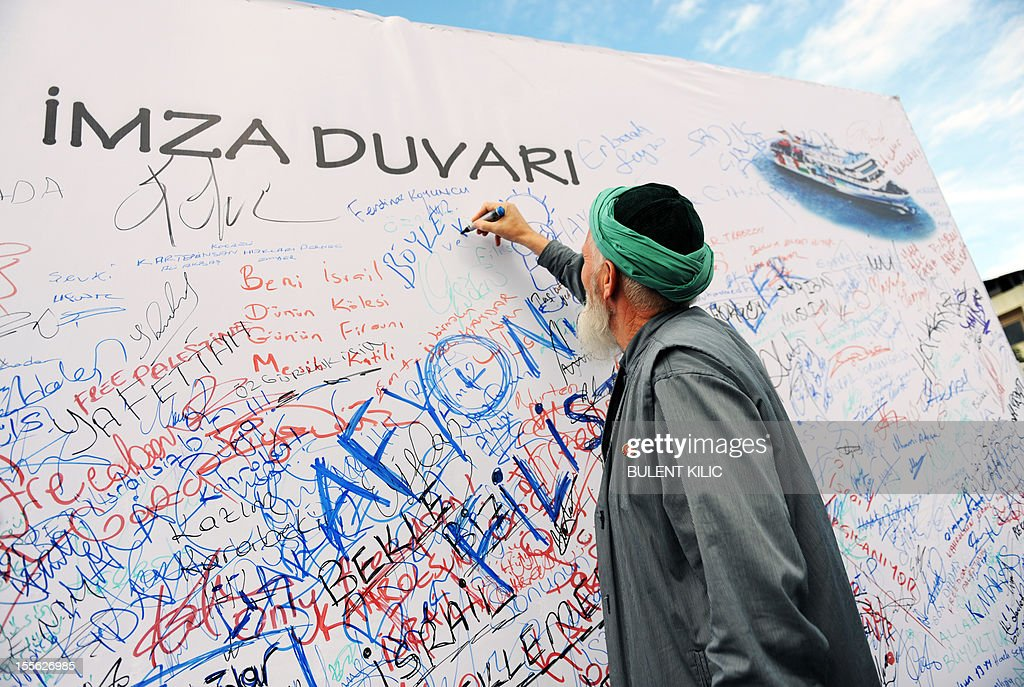A Turkish muslim man signs a board during a demonstration outside the courtroom on November 6, 2012, in Istanbul. Four Israeli ex-military chiefs went on trial in absentia in an Istanbul court over a deadly 2010 raid on a Gaza-bound Turkish ship in what Israel branded a 'show trial' by its former ally. Prosecutors are seeking life sentences for the four over the night-time assault in international waters in the Mediterranean Sea that plunged relations between Israel and Turkey into deep crisis.