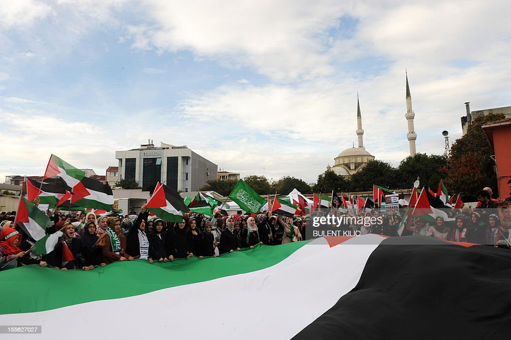 Turkish muslim protesters hold a giant Palestinian flag as they gather in front of the courtroom, on November 6, 2012, in Istanbul. Four Israeli ex-military chiefs went on trial in absentia in an Istanbul court over a deadly 2010 raid on a Gaza-bound Turkish ship in what Israel branded a 'show trial' by its former ally. Prosecutors are seeking life sentences for the four over the night-time assault in international waters in the Mediterranean Sea that plunged relations between Israel and Turkey into deep crisis.