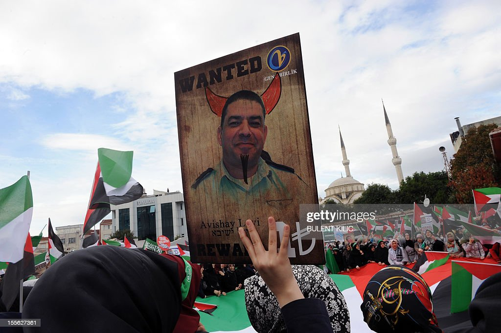 A Turkish muslim woman holds a picture mocking Israel's former head of Air Force intelligence Avishai Levy during a demonsration in front of the courtroom, on November 6, 2012, in Istanbul. Four Israeli ex-military chiefs went on trial in absentia in an Istanbul court over a deadly 2010 raid on a Gaza-bound Turkish ship in what Israel branded a 'show trial' by its former ally. Prosecutors are seeking life sentences for the four over the night-time assault in international waters in the Mediterranean Sea that plunged relations between Israel and Turkey into deep crisis. AFP PHOTO/BULENT KILIC