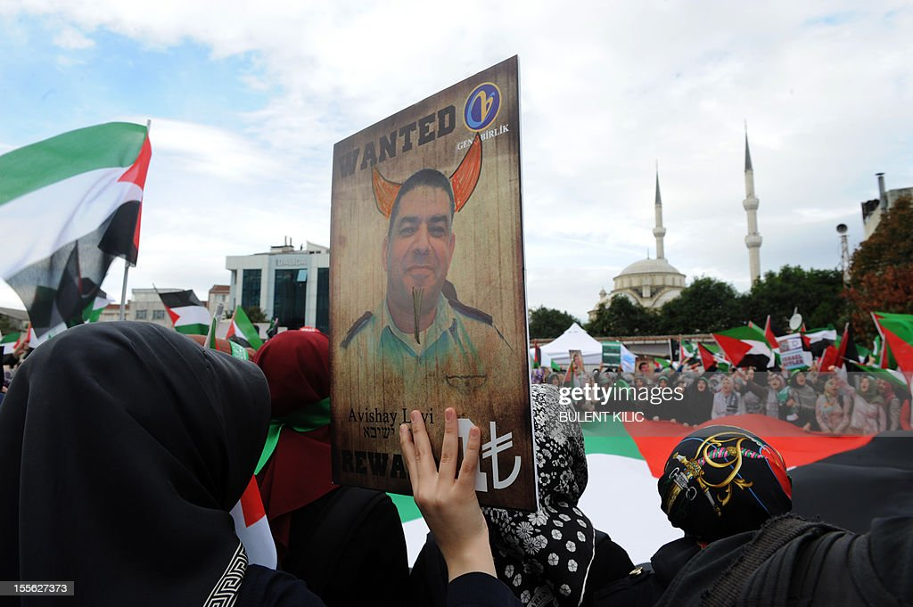 A Turkish muslim woman holds a picture mocking Israel's former head of Air Force intelligence Avishai Levy during a demonsration in front of the courtroom, on November 6, 2012, in Istanbul. Four Israeli ex-military chiefs went on trial in absentia in an Istanbul court over a deadly 2010 raid on a Gaza-bound Turkish ship in what Israel branded a 'show trial' by its former ally. Prosecutors are seeking life sentences for the four over the night-time assault in international waters in the Mediterranean Sea that plunged relations between Israel and Turkey into deep crisis.