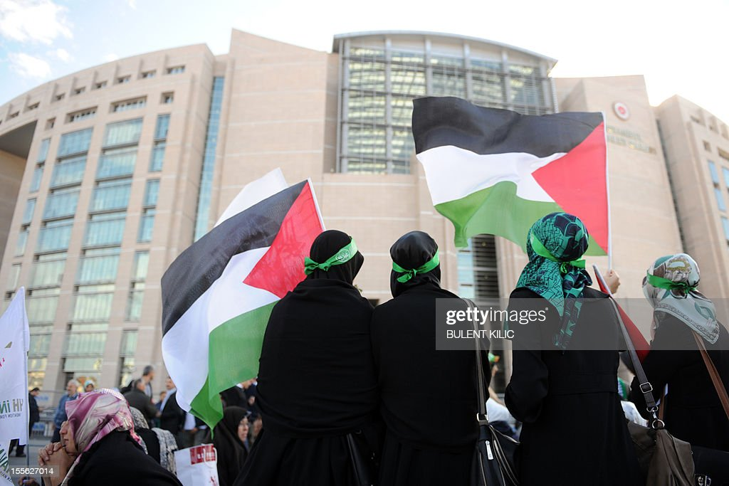Turkish muslim women hold Palestinian flags as protesters gathered in front of the courtroom, on November 6, 2012, in Istanbul. Four Israeli ex-military chiefs went on trial in absentia in an Istanbul court over a deadly 2010 raid on a Gaza-bound Turkish ship in what Israel branded a 'show trial' by its former ally. Prosecutors are seeking life sentences for the four over the night-time assault in international waters in the Mediterranean Sea that plunged relations between Israel and Turkey into deep crisis.