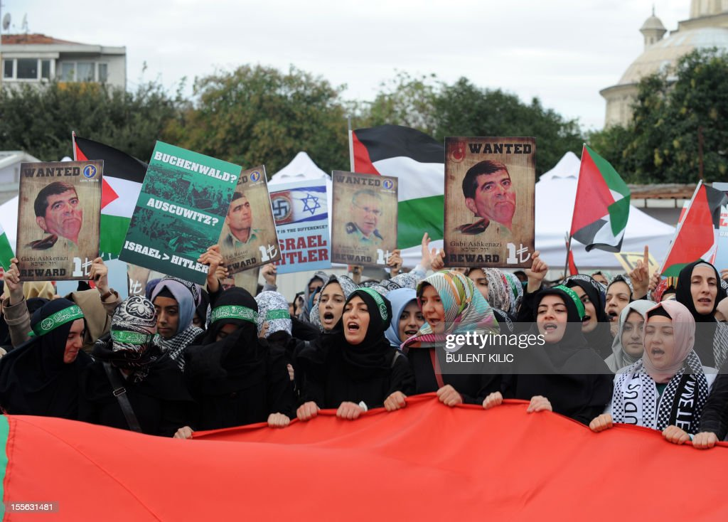 Turkish muslim women hold pictures mocking Israel's former military heads and Palestinian flags during a demonstration in front of the courtroom, on November 6, 2012, in Istanbul. Four Israeli ex-military chiefs went on trial in absentia in an Istanbul court over a deadly 2010 raid on a Gaza-bound Turkish ship in what Israel branded a 'show trial' by its former ally. Prosecutors are seeking life sentences for the four over the night-time assault in international waters in the Mediterranean Sea that plunged relations between Israel and Turkey into deep crisis.