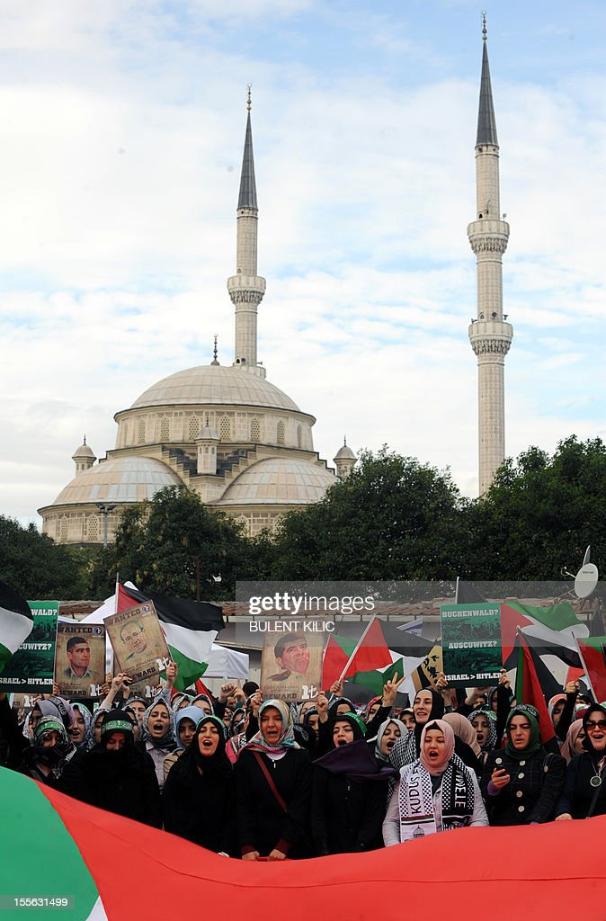 Turkish muslim women hold pictures mocking Israel's former military heads and wave Palestinian flags during a demonstration in front of the courtroom, on November 6, 2012, in Istanbul. Four Israeli ex-military chiefs went on trial in absentia in an Istanbul court over a deadly 2010 raid on a Gaza-bound Turkish ship in what Israel branded a 'show trial' by its former ally. Prosecutors are seeking life sentences for the four over the night-time assault in international waters in the Mediterranean Sea that plunged relations between Israel and Turkey into deep crisis.