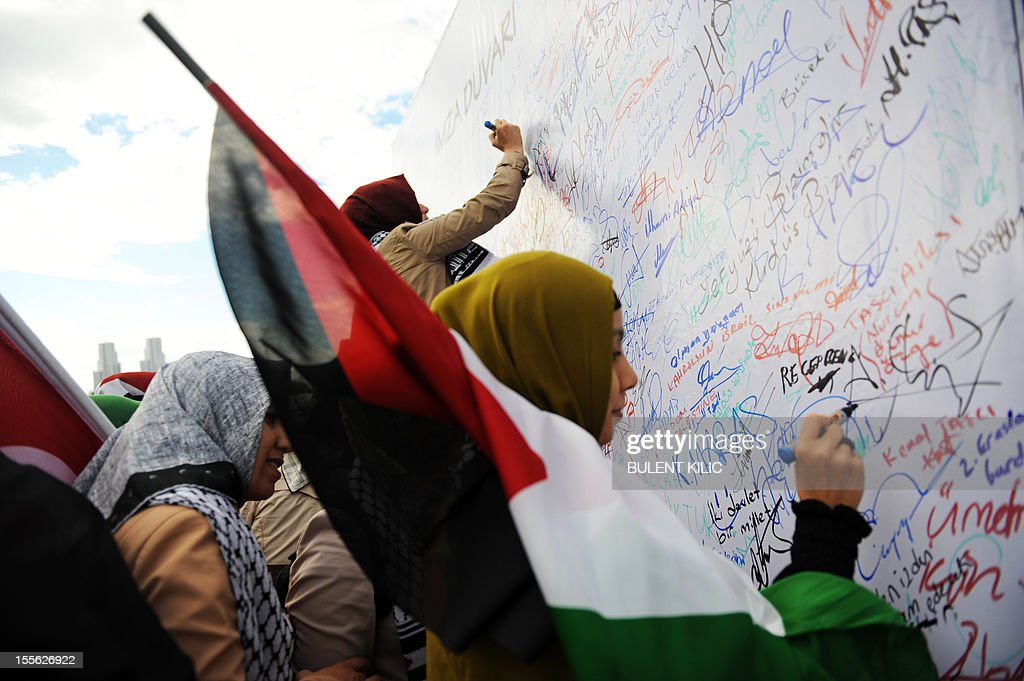 Turkish muslim women sign a board during a demonsration outside the courtroom on November 6, 2012, in Istanbul. Four Israeli ex-military chiefs went on trial in absentia in an Istanbul court over a deadly 2010 raid on a Gaza-bound Turkish ship in what Israel branded a 'show trial' by its former ally. Prosecutors are seeking life sentences for the four over the night-time assault in international waters in the Mediterranean Sea that plunged relations between Israel and Turkey into deep crisis.