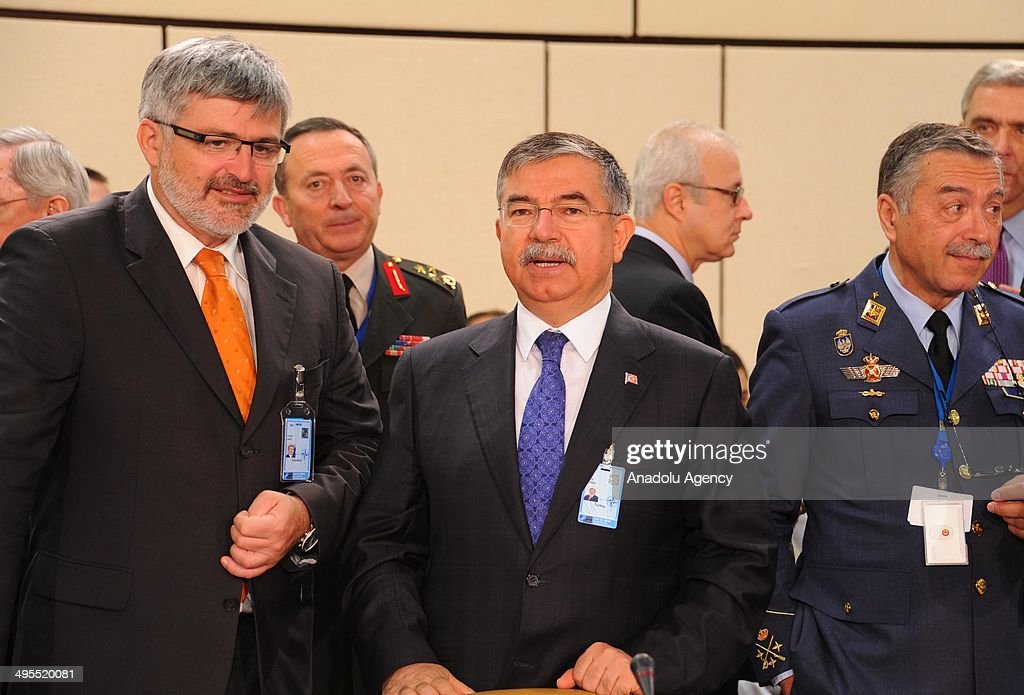 Turkish National Defense Minister Ismet Yilmaz (C) speaks with Slovenian Defence Minister Roman Jakic (L) on the second day of defence ministers meeting in Brussels, Belgium on June 4, 2014. NATO defense ministers met with their Georgian counterparts on Wednesday to discuss security and cooperation issues.