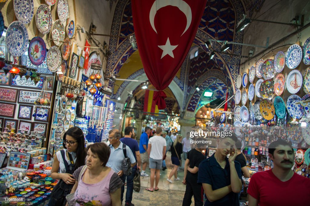 A Turkish national flag hangs above tourist souvenir stores in the Grand Bazaar covered market in Istanbul, Turkey, on Friday, June 14, 2013. The law forbids the sale of alcohol at night and near schools and mosques, going against the secular traditions of the Muslim-majority country of 74 million, where many people drink and women often choose not to cover their hair. Photographer: Lam Yik Fei/Bloomberg via Getty Images