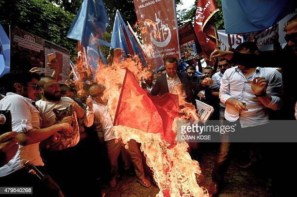 Turkish nationalists burn a Chinese flag during a protest to denounce China's treatment of ethnic Uighur Muslims in front of the Chinese consulate in...