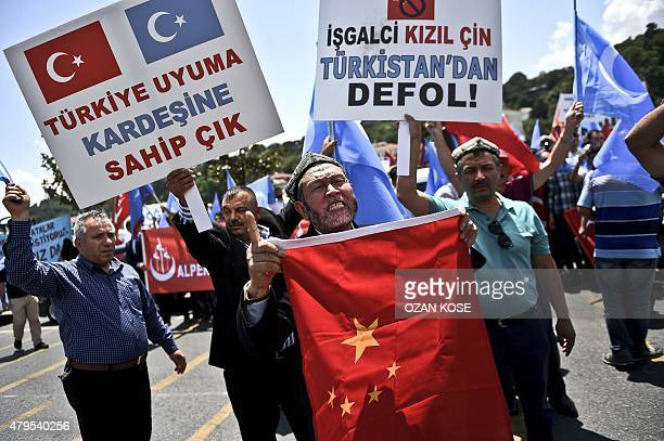 Turkish nationalists holds placards reading 'Turkey save your BrotherChina get out from east Turkhistan' and hold a Chinese flag during a protest to...
