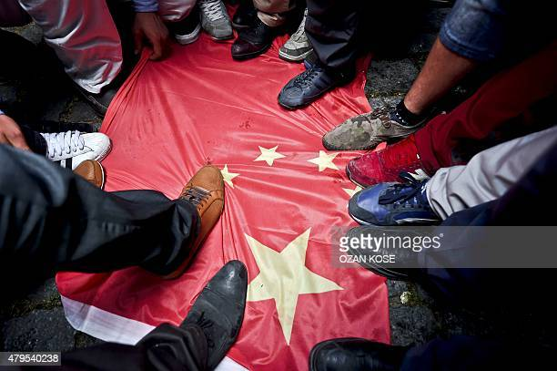 Turkish nationalists step on a Chinese flag during a protest to denounce China's treatment of ethnic Uighur Muslims in front of the Chinese consulate...