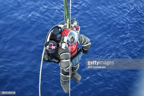 A Turkish Navy diver in an atmosphere diving suit is lifting into the water before a dive from onboard the Turkish Navy's submarine rescue mother...