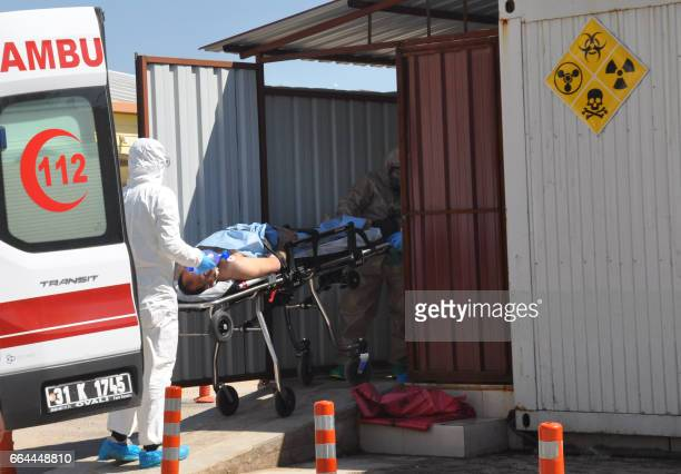Turkish officials with chemical clothes carry a injured man on April 4 2017 in Hatay province near the Syrian border Turkish President Recep Tayyip...