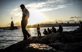 Turkish people gather by the Bosphorus at sunset on July 4 2014 at Uskudar during the holy month of Ramadan in Istanbul Muslim believers abstain from...
