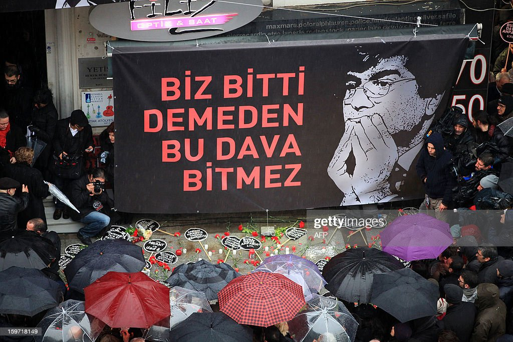 Turkish people gather in front of the offices of Armenian newspaper 'Agos' during a commemoration ceremony for slain journalist Hrant Dink ,in Istanbul, on January 19, 2013. Dink, one of the most prominent voices of Turkey's shrinking Armenian community, was killed by a gunman on January 19, 2007. The 52-year-old Dink, a prominent member of Turkey's tiny Armenian community, campaigned for reconciliation but was hated by Turkish nationalists for calling the World War I massacres of Armenians a genocide. AFP PHOTO/MIRA