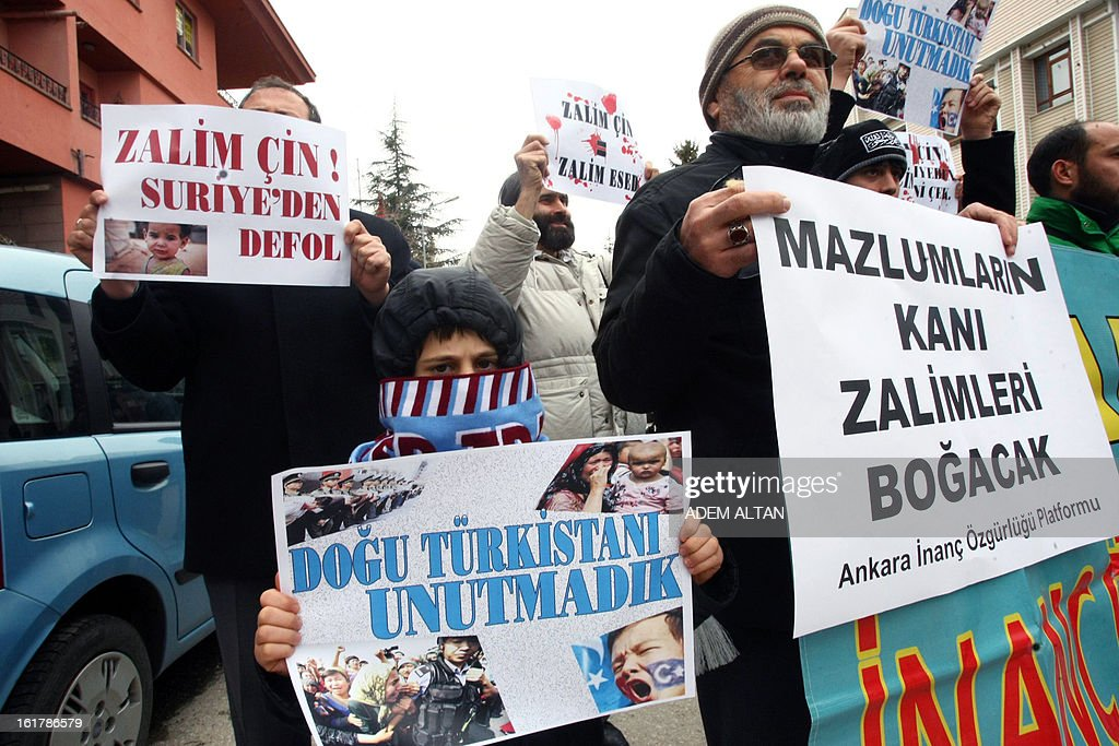 Turkish people hold signs reading '' 'Tyrant China, tyrant Assad,' and 'Tyrant China, get out of Syria!' as they protest against China's policies on Syria and its support to the regime of Syrian President Bashar al-Assad, in front of the Chinese embassy in Ankara, on February 16, 2013. China has backed Russia in supporting Syrian President Bashar Al-Assad, vetoing UN Security Council resolutions that would have put greater pressure on his regime. Beijing has also repeatedly urged dialogue to end the violence. AFP PHOTO / ADEM ALTAN