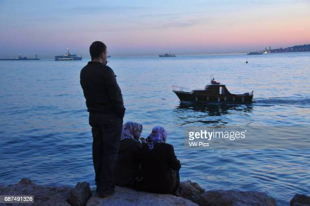 Turkish people relax on the skÙdar waterfront at sunset The Sea of Marmara can be seen in the far distance