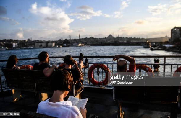 TOPSHOT Turkish people travel on a ferry boat from the European side of Istanbul to the Anatolian side on August 16 2017 / AFP PHOTO / BULENT KILIC