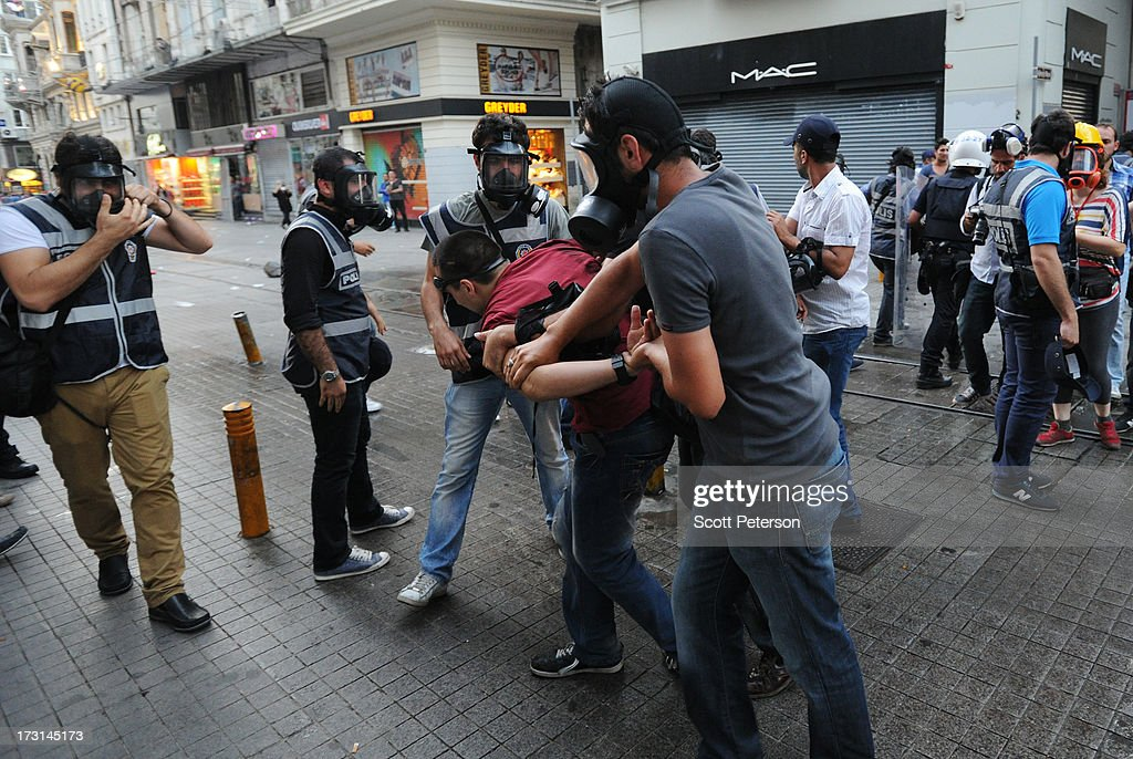 Turkish police arrest a protestor, as they battle anti-government protestors along the Istiklal shopping street near Taksim Square on July 8, 2013 in Istanbul, Turkey. The protests began in late May over the Gezi Park redevelopment project and saving the park trees adjacent to Taksim Square but swiftly turned into a protest aimed at Prime Minister Recep Tayyip Erdogan and what protestors call his increasingly authoritarian rule. The protest spread to dozens of cities in Turkey, in secular anger against Mr. Erdogan and his Islam-rooted Justice and Development Party (AKP).