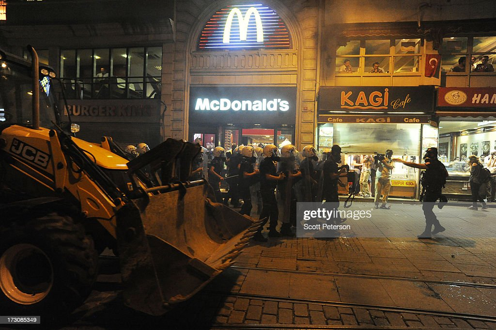 Turkish police battle anti-government protestors along the Istikhlal shopping avenue, with a bulldozer beside a McDonald's, near Taksim Square on July 6, 2013 in the heart of Istanbul, Turkey. The protests began in late May over the Gezi Park redevelopment project and saving the park trees adjacent to Taksim Square but swiftly turned into a protest aimed at Prime Minister Recep Tayyip Erdogan and what protestors call his increasingly authoritarian rule. The protest spread to dozens of cities in Turkey, in secular anger against Erdogan and his Islam-rooted Justice and Development Party (AKP).