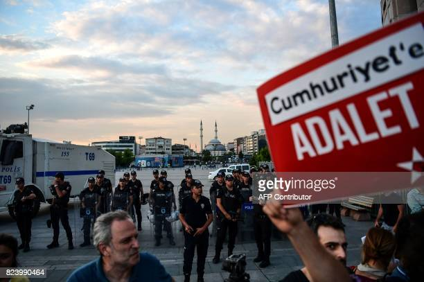 Turkish police forces stand guard as a protester holds a sign reading 'Justice for Cumhuriyet' during a demonstration in Istanbul on July 28 2017...