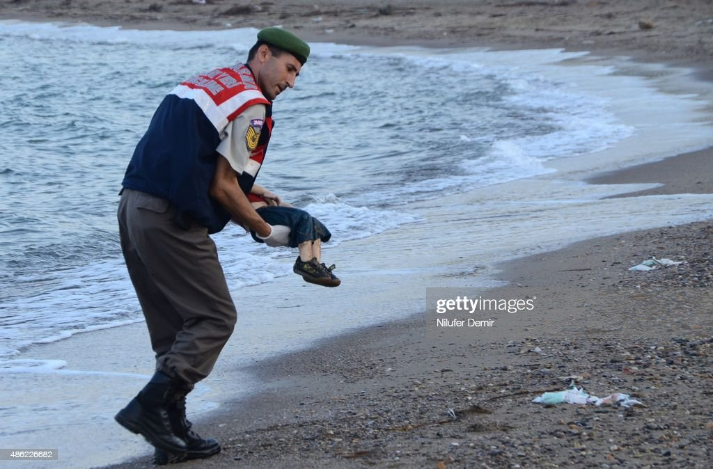 Turkish police officer carries a migrant child's dead body (Aylan Shenu) off the shores in Bodrum, southern Turkey, on September 2, 2015 after a boat carrying refugees sank while reaching the Greek island of Kos. Thousands of refugees and migrants arrived in Athens on September 2, as Greek ministers held talks on the crisis, with Europe struggling to cope with the huge influx fleeing war and repression in the Middle East and Africa. / AFP / DOGAN NEWS AGENCY / Nilufer Demir