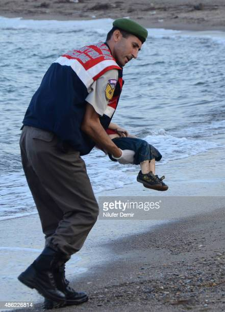 Turkish police officer carries a migrant child's dead body off the shores in Bodrum southern Turkey on September 2 2015 after a boat carrying...