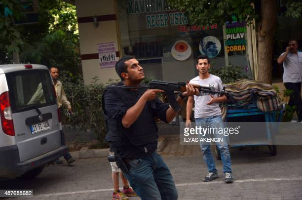 A Turkish police officer holds his AK47 moments after a police officer was shot in the center of Diyarbakir southeast Turkey as police officers had...