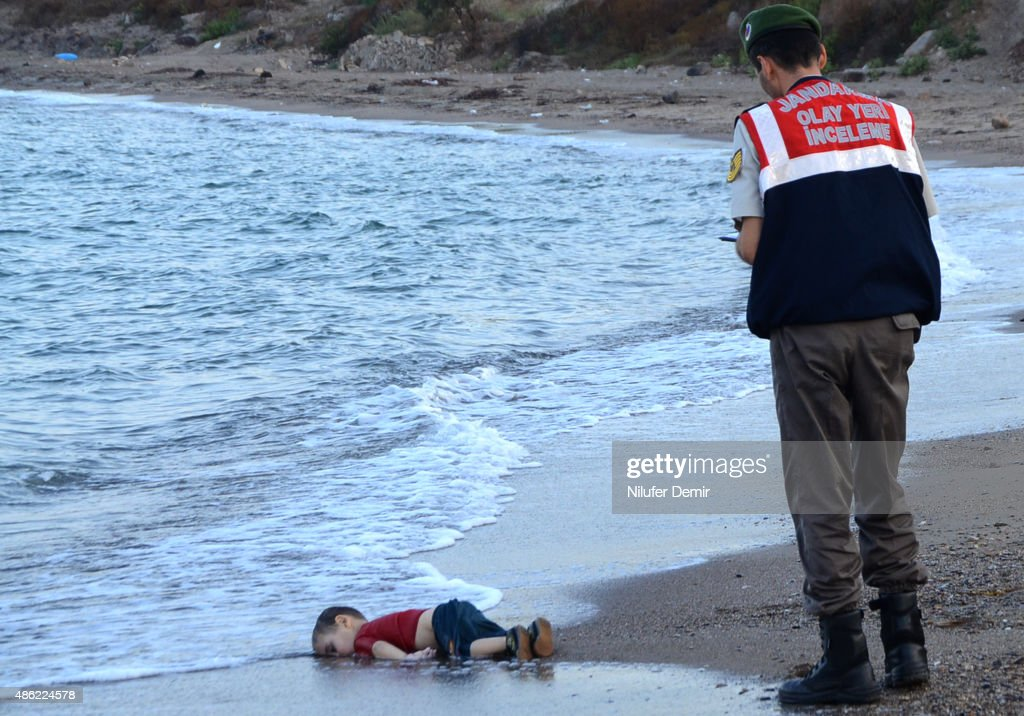 Turkish police officer stands next to a migrant child's dead body (Aylan Shenu) off the shores in Bodrum, southern Turkey, on September 2, 2015 after a boat carrying refugees sank while reaching the Greek island of Kos. Thousands of refugees and migrants arrived in Athens on September 2, as Greek ministers held talks on the crisis, with Europe struggling to cope with the huge influx fleeing war and repression in the Middle East and Africa. / AFP / DOGAN NEWS AGENCY / Nilufer Demir