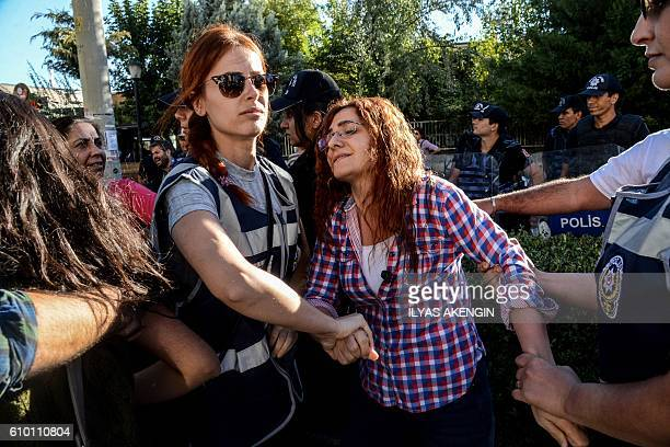 TOPSHOT Turkish police officers arrest a teacher during a demonstration to protest against the suspension of teachers for suspected links with...