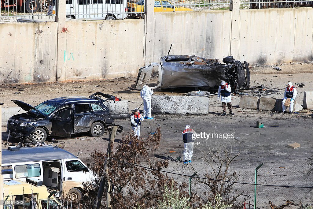 Turkish police officers clean on February 13, 2013 the site where a vehicle exploded on February 11 in the buffer zone between Turkey's Cilvegozu border crossing and Syria's Bab al-Hawa post, which was seized by Syrian rebels in July. Fourteen people died in the blast. AFP PHOTO/MIRA