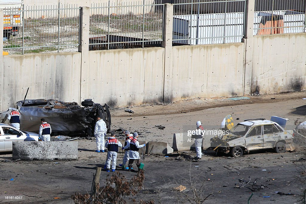 Turkish police officers clean on February 13, 2013 the site where a vehicle exploded on February 11 in the buffer zone between Turkey's Cilvegozu border crossing and Syria's Bab al-Hawa post, which was seized by Syrian rebels in July. Fourteen people died in the blast.