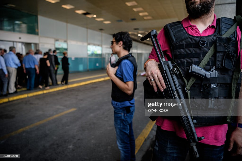 Turkish police officers stand guard as Consuls of European countries lay cloves and roses at the explosion site at Ataturk airport International terminal on July 1, 2016 three days after a suicide bombing and gun attack targeted Istanbul's Ataturk airport, killing 44 people. Although no group has yet claimed Tuesday's gun and bomb attack which killed 42 people, Ankara has pointed a finger at IS, which has been blamed for several suicide attacks around the country in the past year. / AFP / OZAN