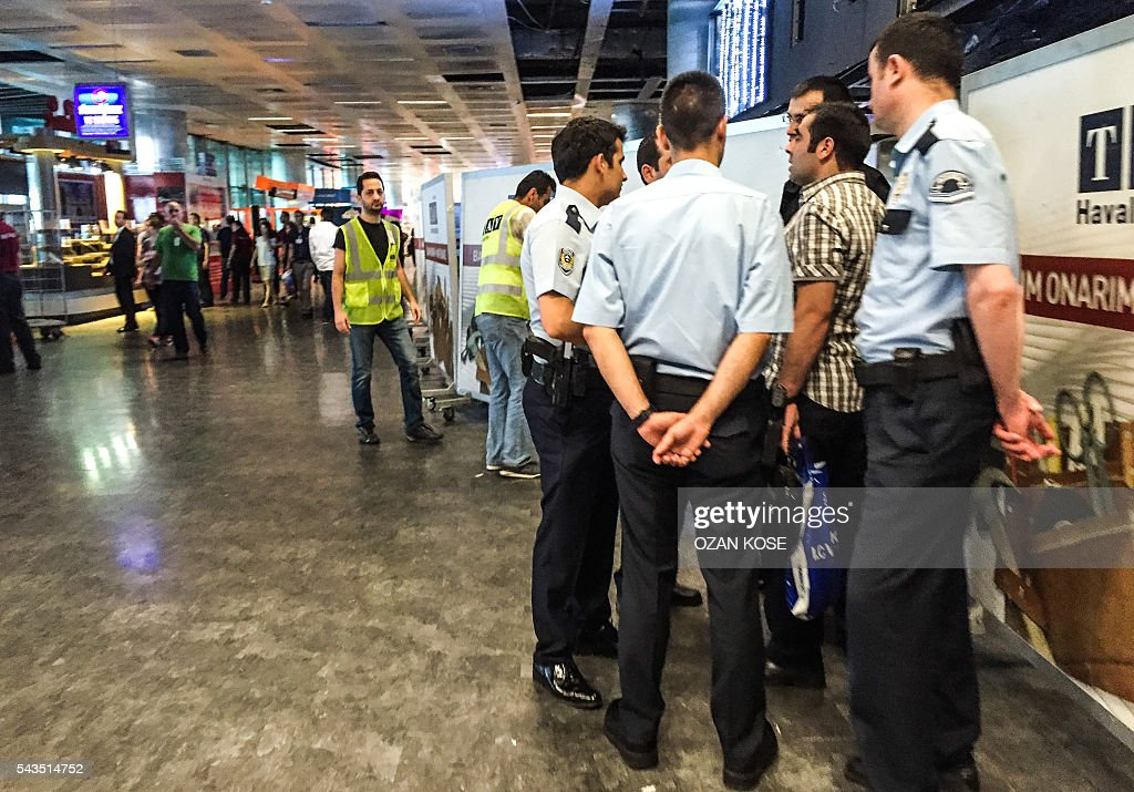 Turkish police officers talk with a man at the attacks and explosions site in Ataturk airport's international arrivals terminal on June 29, 2016, a day after a suicide bombing and gun attack targeted Istanbul's airport, killing at least 36 people. A triple suicide bombing and gun attack that occurred on June 28, 2016 at Istanbul's Ataturk airport has killed at least 36 people, including foreigners, with Turkey's prime minister saying early signs pointed to an assault by the Islamic State group. / AFP / OZAN