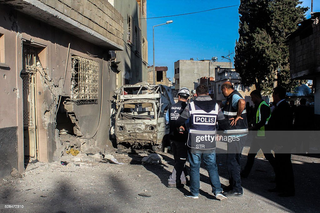 Turkish police officers work at the site after a rocket hit a house on May 5, 2016 in Kilis. One person was killed and seven more wounded when rockets fired from Syria slammed into the Turkish border region of Kilis, which has been regularly targeted by jihadists this year, the Dogan news agency said. / AFP / STR