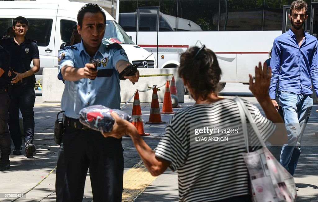 Turkish police points his gun to a woman asking her to leave the package she is carrying in front of the courthouse in Ankara on July 18 as some 7500...