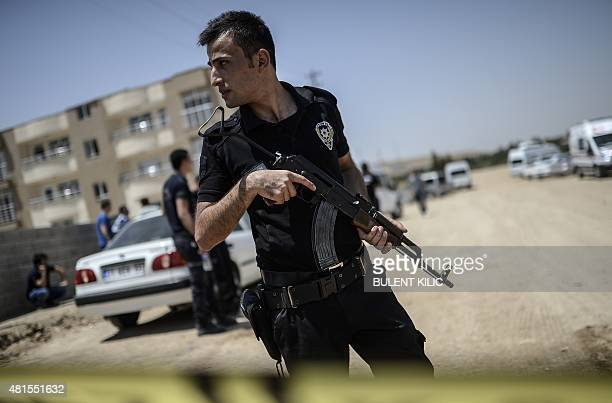 Turkish police stand near a building where two police officers were found shot dead at their home on July 22 2015 in the Turkish town of Ceylanpinar...