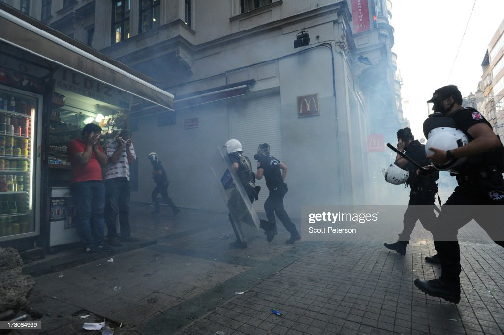 Turkish police use tear gas and water cannons to battle anti-government protestors along the Istikhlal shopping avenue near Taksim Square on July 6, 2013 in the heart of Istanbul, Turkey. The protests began in late May over the Gezi Park redevelopment project and saving the park trees adjacent to Taksim Square but swiftly turned into a protest aimed at Prime Minister Recep Tayyip Erdogan and what protestors call his increasingly authoritarian rule. The protest spread to dozens of cities in Turkey, in secular anger against Erdogan and his Islam-rooted Justice and Development Party (AKP).