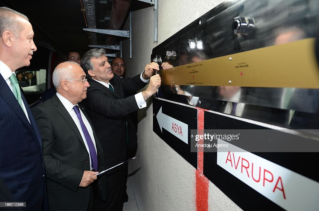 Turkish President Abdullah Gul (R) fastens a board as Turkish Prime Minister Recep Tayyip Erdogan (R) and Parliament Speaker Cemil Cicek (C) look next to the red line representatively connecting Europe and Asia, after the inauguration ceremony of the Marmaray, the railway tunnel underneath the Bosphorus Strait linking European and Asian sides of Istanbul, on October 29, 2013 Istanbul, Turkey.