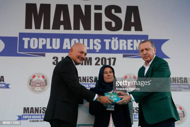Turkish President Recep Tayyip Erdogan and Chairman of Turkey's Dogus Holding Ferit Sahenk gives a key of a house for relatives of victims who lost...