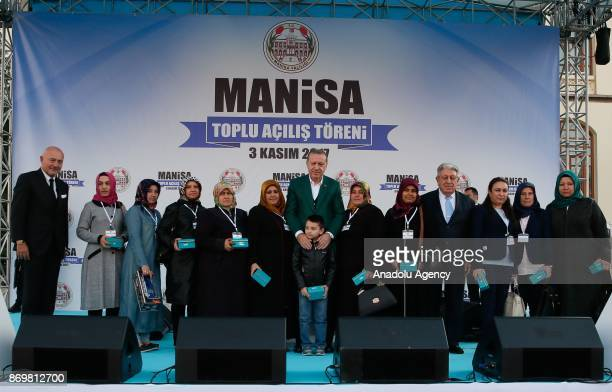 Turkish President Recep Tayyip Erdogan and Chairman of Turkey's Dogus Holding Ferit Sahenk poses for a photo with relatives after they gave a key of...