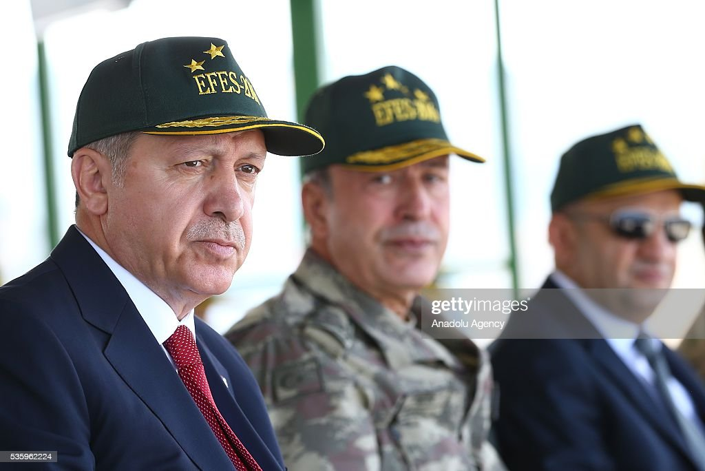 Turkish President Recep Tayyip Erdogan (L) and Chief of the General Staff of the Turkish Armed Forces, Hulusi Akar (C) attend the Efes-2016 Combined Joint Live Fire Exercise at Seferihisar district of Izmir, Turkey on May 31, 2016. The Turkish-led multinational military exercises, Efes-2016 which started at 04 May and will be finished at 04 June 2016, aims to train participating units and staff in planning and conducting combined and joint operations, including logistics and command-control as well as to improve the level of interoperability among headquarters and forces.